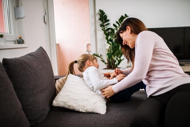 Profiter des moments de plaisir. mère chatouillant sa fille à la maison. Photo Premium