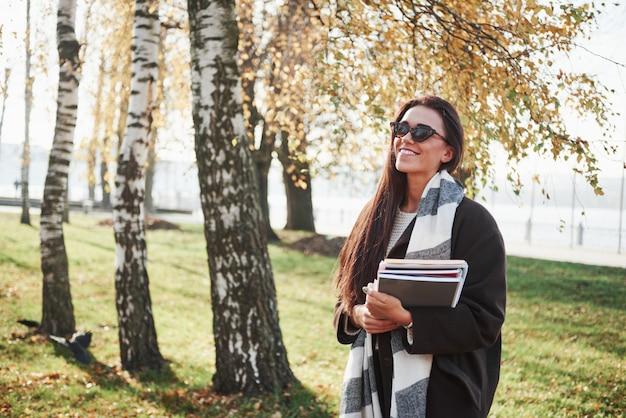 Profiter De La Nature Et Des Journées Chaudes. Jeune Brune Souriante à Lunettes Se Tient Dans Le Parc Près Des Arbres Et Détient Le Bloc-notes Photo gratuit