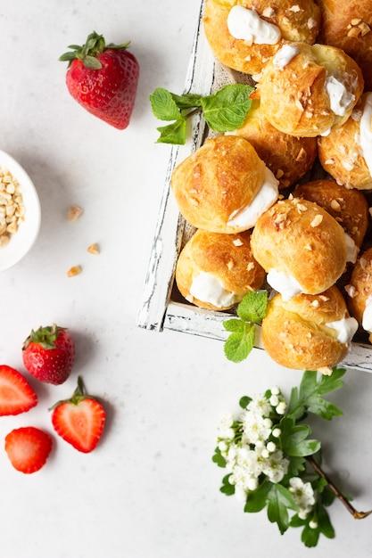 Profiteroles (boulettes De Choux à La Française Avec Fromage Cottage Et Crème à La Fraise, Menthe Et Tasse De Café). Photo Premium