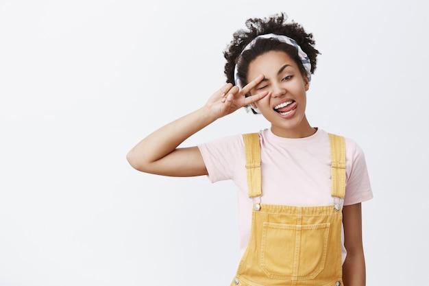 Profitez De La Vie Et Détendez-vous. Portrait De Joyeux Insouciant Belle Afro-américaine En Salopette Jaune Et Bandeau, Tête Inclinable, Montrant La Langue Et Faisant Signe De Paix Sur Les Yeux, Clignant Des Yeux, S'amusant Photo gratuit