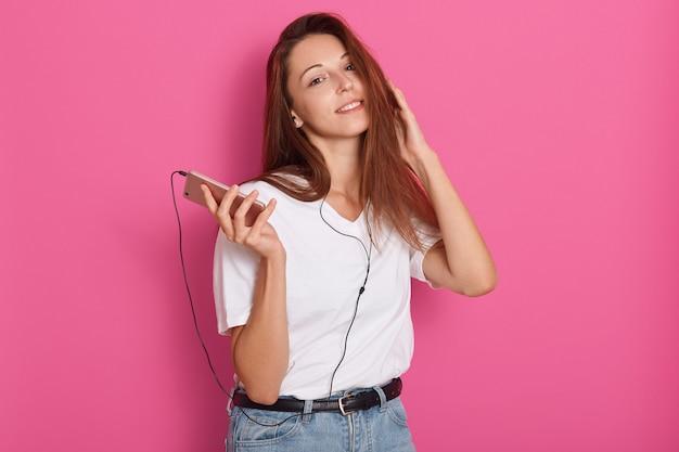 Projectile Studio, De, Jeune Femme, écouter Musique, à, écouteurs, Tenue, Smartphone, Dans, Mains, Regarder Appareil-photo, Délassant, Chez Soi Photo gratuit