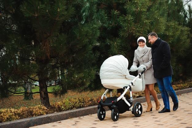 Promenade en famille dans le parc en automne avec un landau. maman, papa et bébé Photo Premium