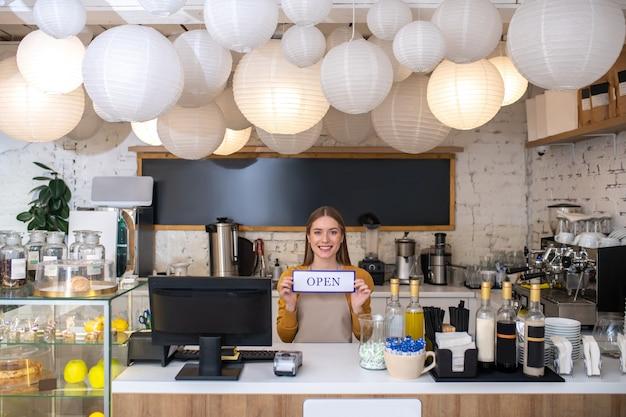 Un Propriétaire De Café Souriant Tenant Le Signe Ouvert Photo Premium
