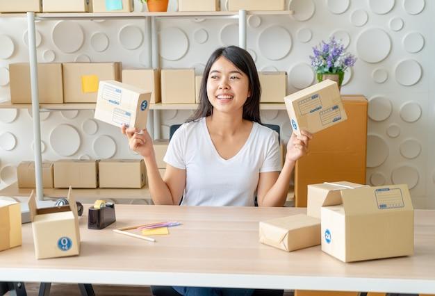 Propriétaire D'entreprise Asiatique Travaillant à La Maison Avec Boîte D'emballage Sur Le Lieu De Travail Photo Premium