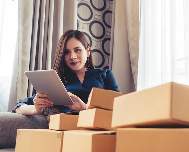 Le propriétaire d'une entreprise en ligne vérifie sa commande sur une tablette Photo Premium
