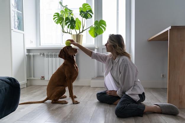 Propriétaire De Femme Heureuse Avec Son Chien Vizsla Jouant Avec Une Balle De Tennis à La Maison, Assis Sur Le Sol Photo Premium