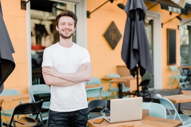 Propriétaire de petite entreprise devant son café avec ordinateur portable Photo Premium