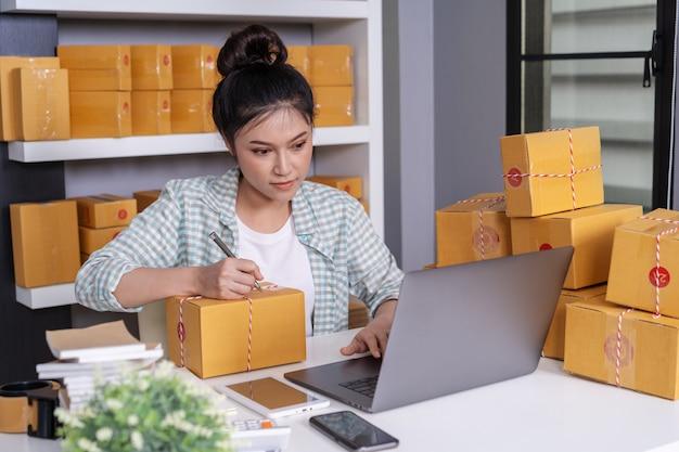 Propriétaire d'une petite entreprise en ligne, femme travaillant avec un ordinateur portable, prépare des boîtes à colis pour livraison au client Photo Premium