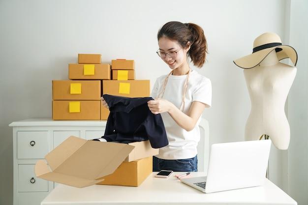 Propriétaire de petite entreprise en ligne, jeune entreprise à démarrer propriétaire de vendeur en ligne à l'aide d'un ordinateur Photo Premium