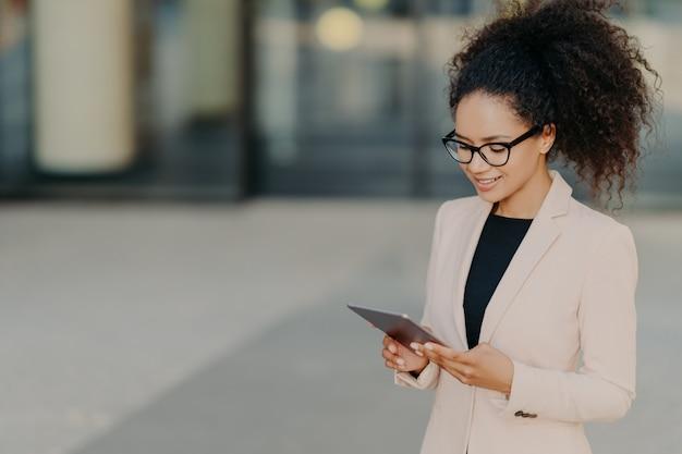 Propriétaire prospère d'une entreprise se dresse avec son pavé tactile numérique, centré sur l'écran Photo Premium