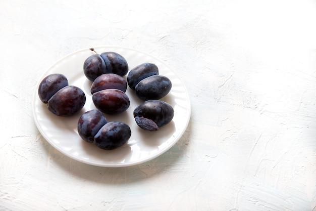 Les Prunes D'accrète Drôles Laides Se Trouvent Sur Une Assiette En Porcelaine Blanche. Concept De Cuisine Végétarienne. Copiez L'espace. Photo Premium