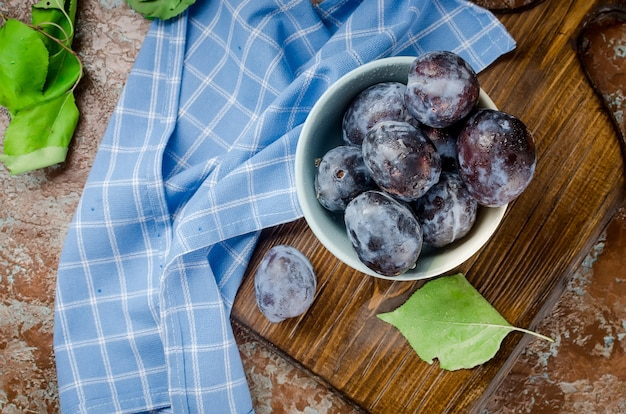 Prunes dans un bol en poterie sur bois rustique foncé Photo Premium