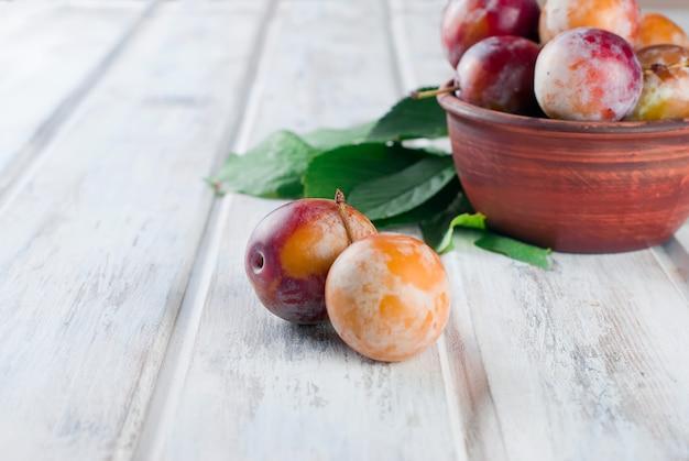 Prunes fraîches du jardin dans un bol sur la vieille table en bois. Photo Premium