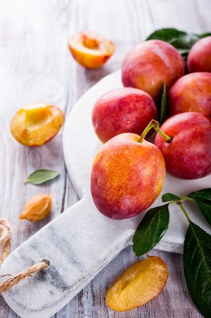 Prunes fraîches sur une planche à découper en marbre Photo Premium