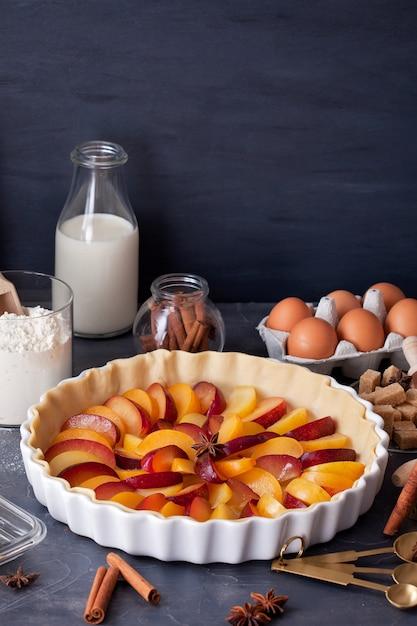 Prunes mûres fraîches dans la tarte maison, les ingrédients de la pâtisserie et l'ustensile de cuisine pour la cuisson Photo Premium
