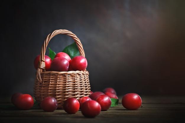 Prunes rouges mûres dans un panier en osier sur une table en bois. Photo Premium
