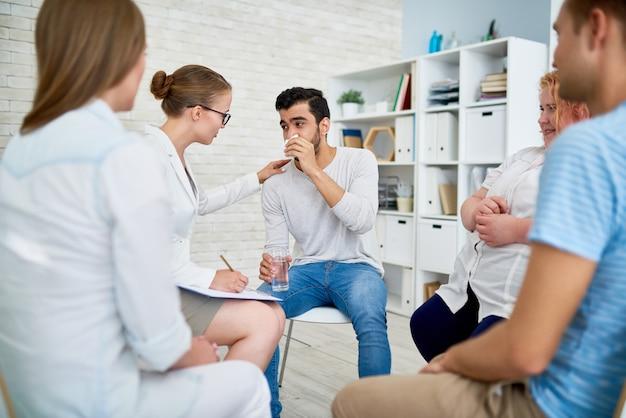 Psychiatre Femelle Consultant Jeune Homme En Session De Groupe Photo Premium