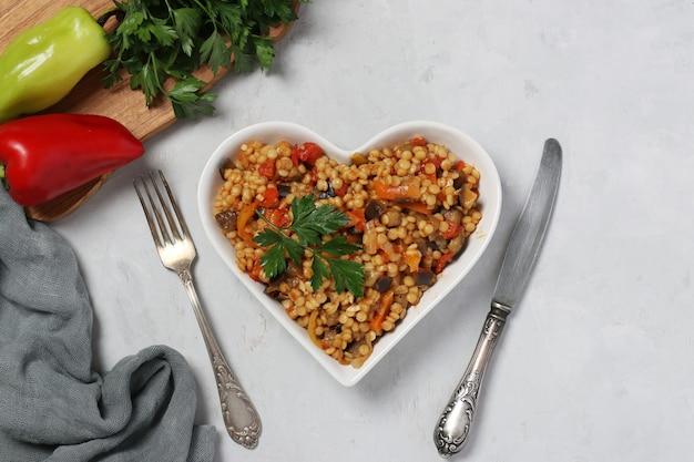 Ptitim De Pâtes Faites Maison Aux Légumes Sur Plaque En Forme De Coeur Sur Table Grise. Vue De Dessus. Format Horizontal. Photo Premium