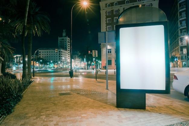 Publicité vide sur le trottoir avec des feux de circulation floues dans la nuit Photo gratuit