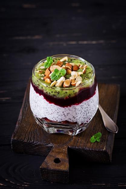 Pudding au chia avec baies fraîches, noix et menthe en verre Photo Premium