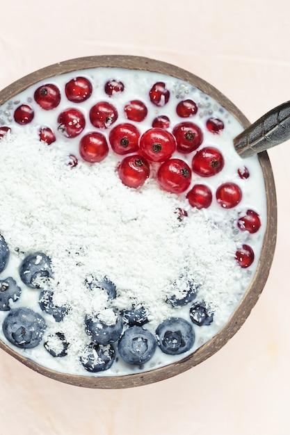 Pudding de graines de chia avec myrtilles, baies de cassis et flocons de noix de coco dans un bol Photo Premium