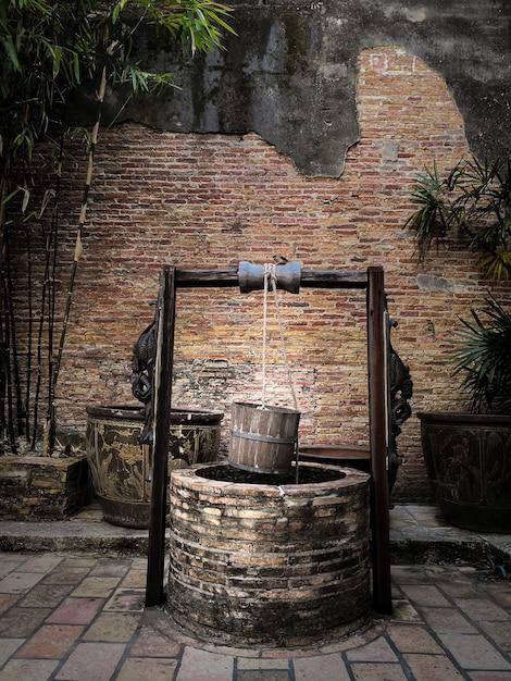 Puits artésien antique avec seau en bois suspendu et toit en bois. Photo Premium