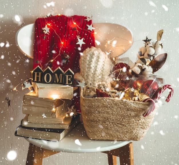 Pull D'hiver Posé Sur Une Chaise Avec Un Panier De Décorations De Noël Photo Premium