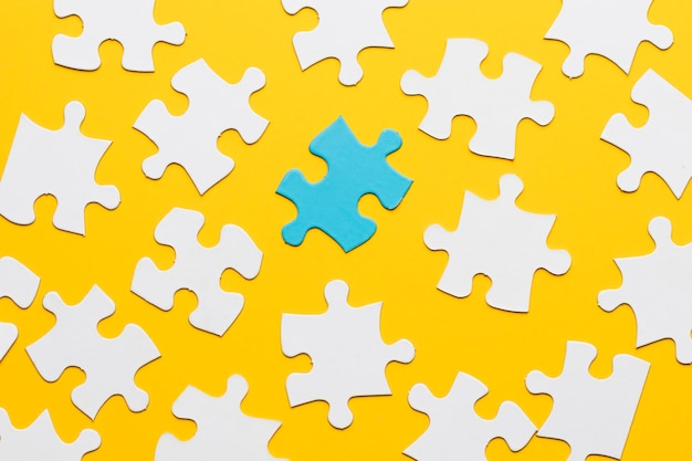 Puzzle bleu avec morceau de puzzle blanc sur fond jaune Photo gratuit