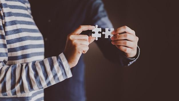 Puzzle tenant par la main de deux personnes Photo Premium