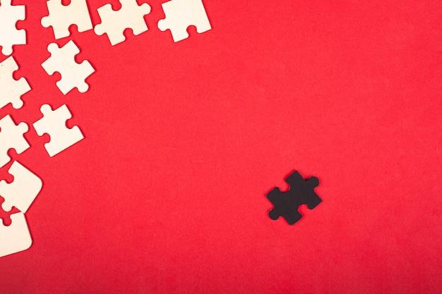Puzzles En Bois Blanc Et Noir Sur Fond Rouge Gros Plan Vue De Dessus. Le Leader Antisocial Exclu Diffère Des Autres Jouets éducatifs Pour Enfants. Photo Premium