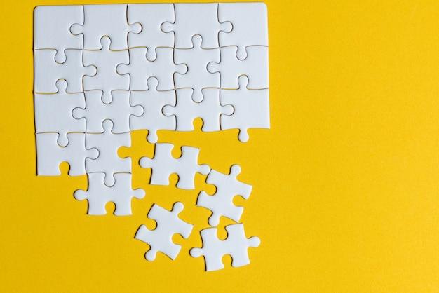 Puzzles placés sur un fond jaune concept créatif avec espace de copie Photo Premium