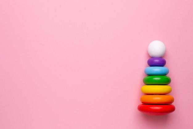 Pyramide En Bois Pour Enfants Colorés Sur Fond Rose, Jouet Pour Les Tout-petits Et Les Bébés Vue De Dessus Avec Copyspace Photo Premium