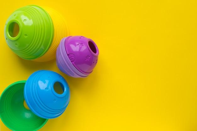 Pyramide colorée de jouets pour enfants. jouets pour le développement des jeunes enfants sur fond jaune. fond Photo Premium