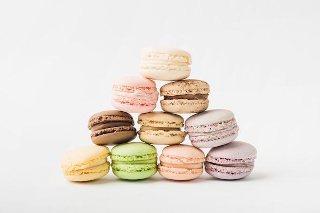 Pyramide de nombreux macarons colorés sur fond blanc Photo gratuit