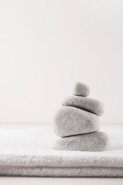 Pyramide des pierres sur une serviette propre pliée isolé sur fond blanc Photo gratuit