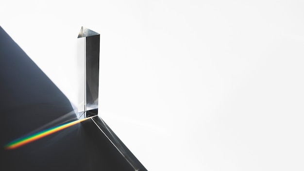 Pyramide triangulaire en verre avec effet de dispersion de la lumière optique sur fond blanc Photo gratuit