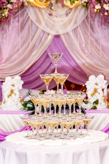 Pyramide de verres à champagne à l'intérieur du mariage pourpre. Photo Premium