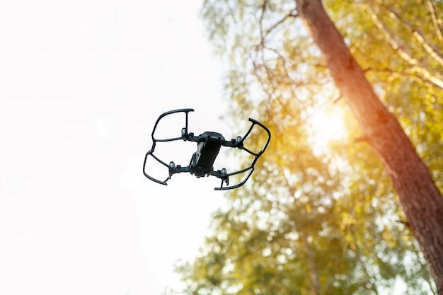 Quadricoptère de petit drone intelligent volant sur un ciel blanc et des arbres verts. Photo Premium