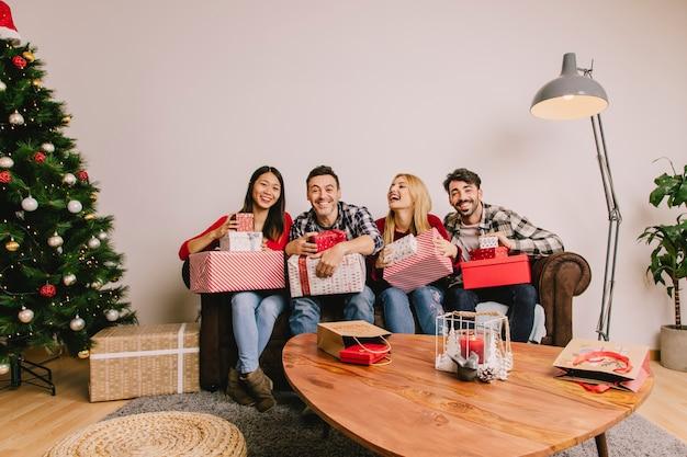 Quatre amis sur le divan se donnent mutuellement Photo gratuit