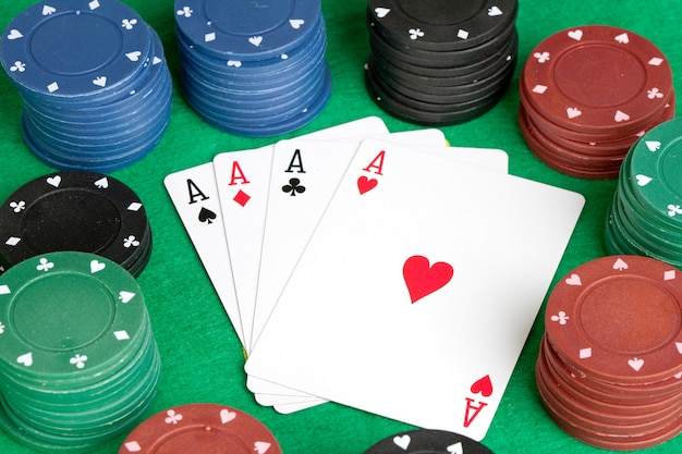 Quatre as et des jetons de poker empilés de plusieurs couleurs Photo Premium