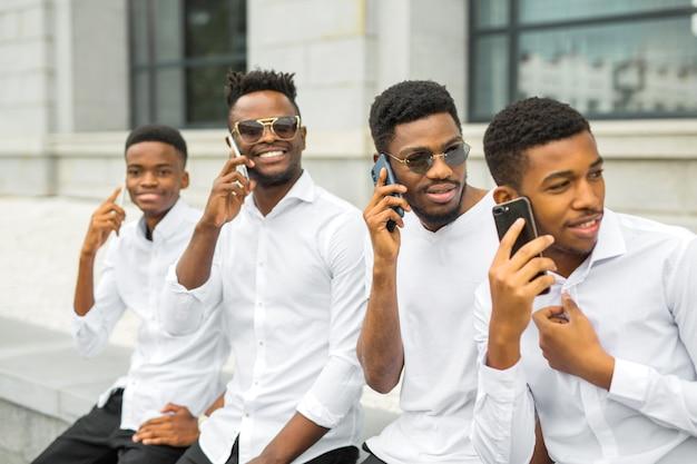 Quatre Beaux Jeunes Hommes Africains En Chemises Blanches Avec Des Téléphones Dans Leurs Mains Photo Premium