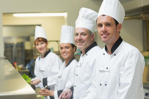 Quatre chefs travaillant dans une cuisine debout dans une rangée Photo Premium