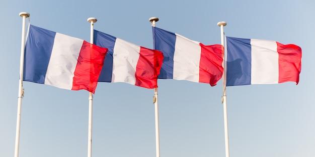 Quatre drapeau français flottant dans le ciel Photo Premium