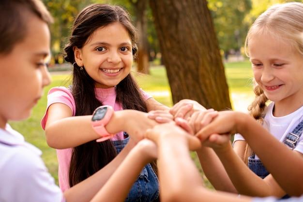 Quatre enfants tenant à la main dans un parc Photo gratuit