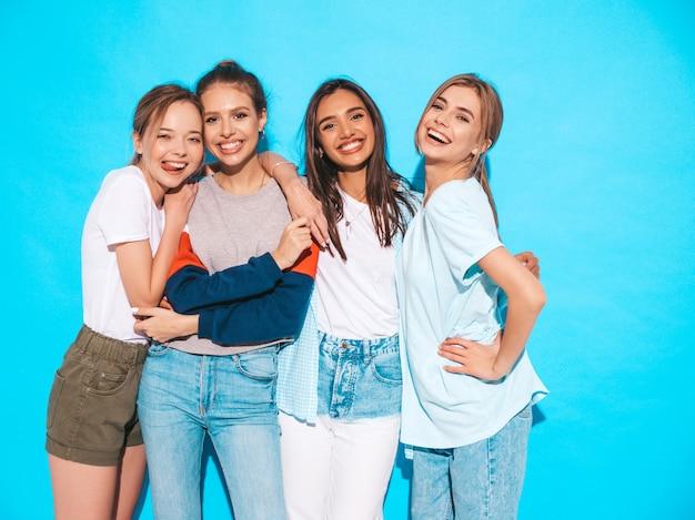 Quatre Jeunes Belles Filles Hipster Souriantes Dans Des Vêtements D'été à La Mode. Femmes Insouciantes Sexy Posant Près Du Mur Bleu En Studio. Modèles Positifs S'amusant Et étreignant Photo gratuit