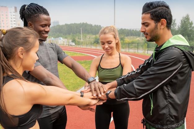 Quatre Jeunes Gens Interculturels En Vêtements De Sport Faisant Pile De Mains En Se Tenant Debout Sur Le Stade Extérieur Photo Premium