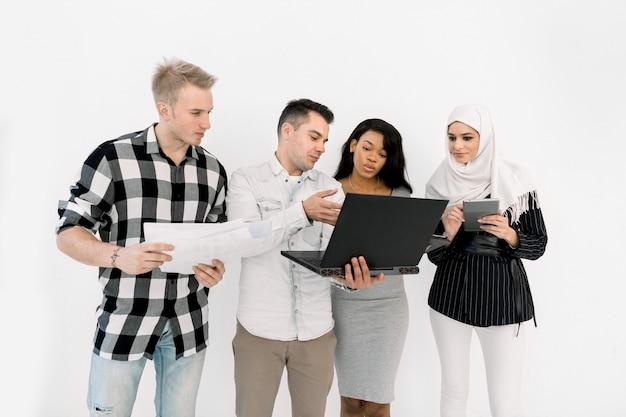 Quatre Jeunes Multiethniques, Filles Africaines Et Musulmanes, Deux Hommes De Race Blanche, Tenant Des Papiers Et Différents Gadgets Photo Premium