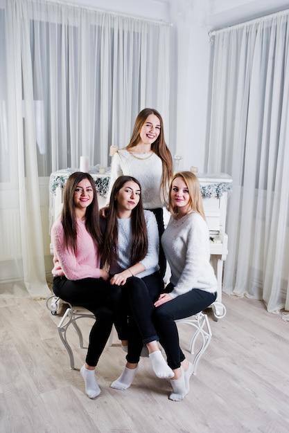 Quatre Jolies Amies Filles Portent Des Chandails Chauds Et Un Pantalon Noir Contre Un Vieux Piano Avec Une Décoration De Noël Dans La Salle Blanche. Photo Premium