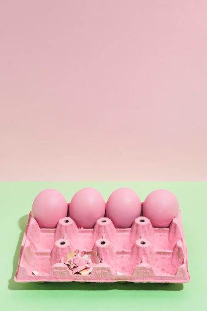 Quatre oeufs de pâques roses dans un grand rack sur une table verte Photo gratuit
