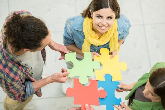 Quatre personnes créatives essayant de relier des pièces du puzzle. Photo Premium